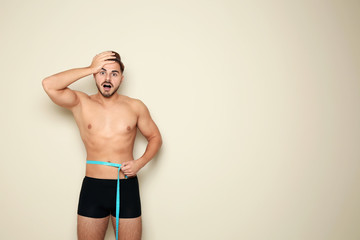Fit man measuring his waist on color background, space for text. Weight loss