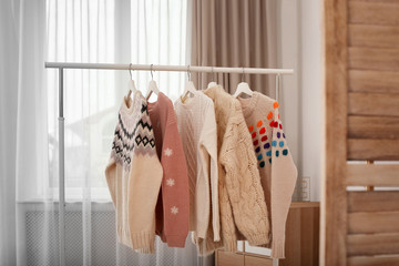 Wardrobe rack with stylish warm clothes indoors