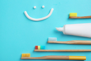 Flat lay composition with smiling face made of toothpaste on color background