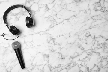 Headphones, microphone and space for text on marble background, top view
