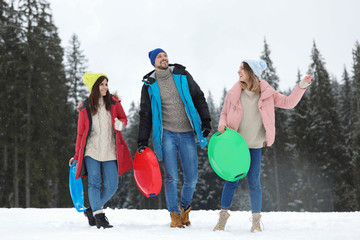 People with plastic sleds outdoors. Winter vacation