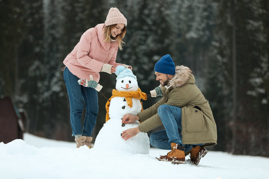 Couple making snowman outdoors. Winter vacation