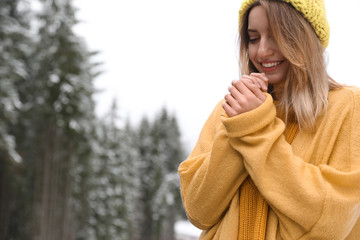 Young woman in warm clothes outdoors, space for text. Winter vacation