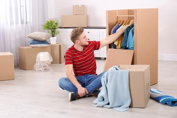 Young man near wardrobe box at home