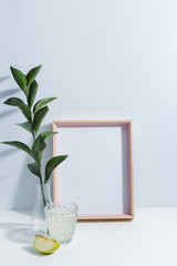 Mock up white frame, green twigs in vase, piece of apple and glass of limonade on book shelf or desk. White colors. White-blue colors. Minimalistic concept.