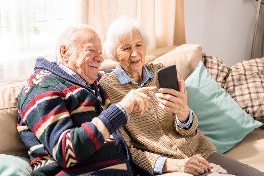 Portrait of adorable senior couple using smartphone together video chatting with family at home, copy space