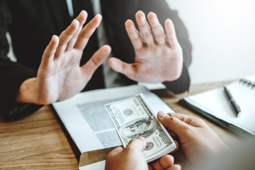 Corruption concept,Businessman manager refusing receive money from Business man passing money dollar bills corruption bribery.
