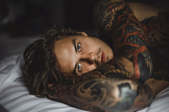 Young handsome tattooed man just woke up and laying in bed in the bedroom.
