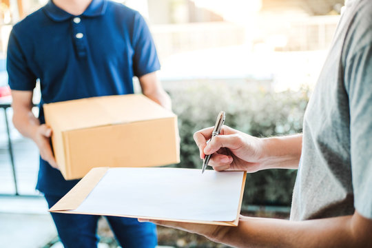 Customer Man signature in clipboard to receive package from professional delivery man at home
