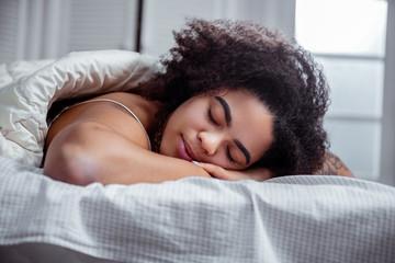 Peaceful dark-skinned woman resting on bed and having nice sleep