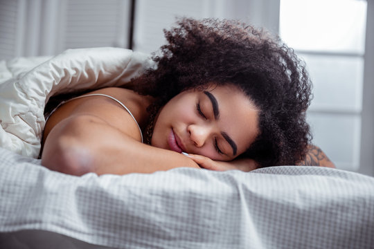 Peaceful dark-skinned woman resting on bed and having nice sleep
