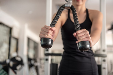 Woman exercising  at the gym on a machine pull down doing cardio workout in fitness club,sport, fitness, lifestyle and people concept - close up of young woman flexing muscles on cable - Image