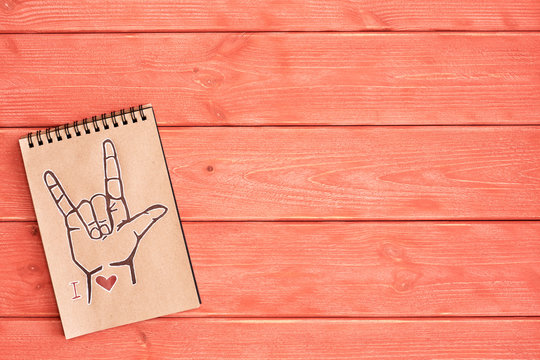 """A notebook of Kraft paper with a painted symbol ASL (American Sign Language) ILY (I Love you) that lies on the textured wooden surface of the color """" Living Coral"""""""