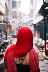 Woman wearing red headscarf walking along street, Varanasi, India