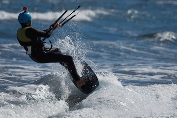 A kite surfer rides the waves, fun in the ocean extreme sport