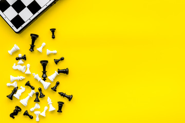 Symbol of competition. Chess board and chess figures on yellow background top view space for text