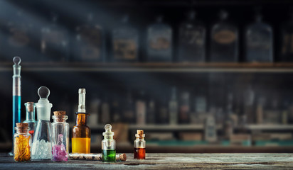 Vintage medications in small bottles on wood desk. Old medical, chemistry and pharmacy history concept background. Retro style.