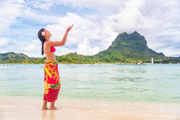 Polynesian hula dancer woman dancing on Bora Bora beach Hawaii traditional dance for luau party. Happy Asian tourist learning to dance in front of Mt Otemanu, Tahiti, French Polynesia.