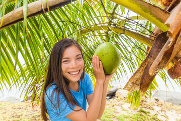 Tahitit tourist woman on coconut farm showing natural fruit hanging on palm tree. Happy Asian girl on tropical vacation holidays.