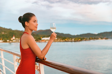 Wall Mural - Luxury cruise ship travel elegant Asian woman drinking wine glass drink enjoying watching sunset from boat deck over ocean in summer vacation destination. Cruising sailing away on holiday.