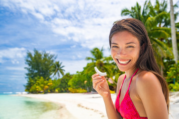Fresh coconut slice Asian woman eating healthy snack on beach holiday. Summer vacation in Tahiti smiling girl holding fruit cut by local at tropical travel destination. Coco water, popular food trend.