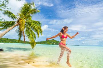Travel Vacation beach woman laughing having fun splashing in water in paradise