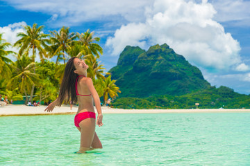 Bora bora luxury vacation travel paradise bikini woman swimming at island in Tahiti, French Polynesia. Popular honeymoon destination holiday in South Pacific, Oceania.