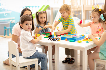 Kindergarten children play color toys with teacher in playroom at preschool. Education concept.