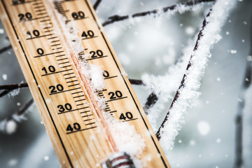 thermometer with subzero temperature stuck in the snow in the winter forest