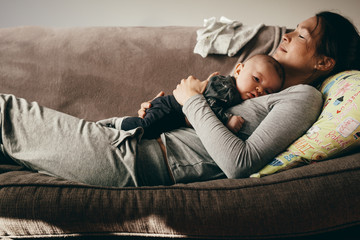 Mother sleeping on a couch with her baby on her Wall mural