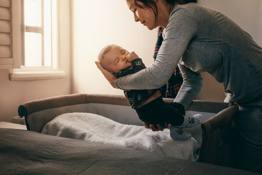 Mother putting her baby to sleep on a bedside baby crib