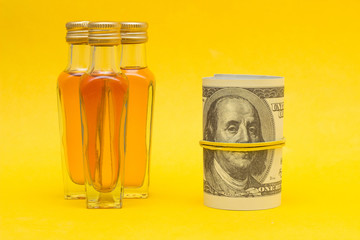 Small bottles with alcohol on a yellow background and money dollars, the proceeds from the sale of alcohol, close-up, photography