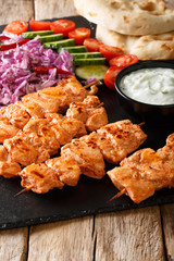 Traditional Taouk chicken kebab with fresh salad, yogurt sauce and pita bread close-up. vertical