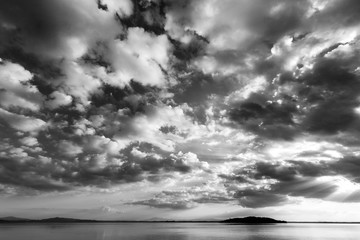 Beautiful wide angle view of a lake with an huge sky with clouds, above an island