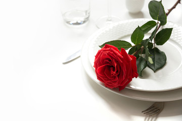 Valentine's day or birthday romantic dinner. Romantic table setting with red rose.
