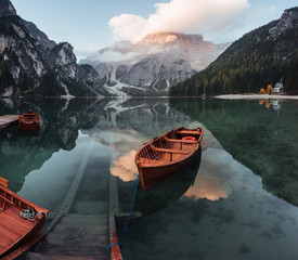 Awesome plase to rest. Wooden boats on the crystal lake with majestic mountain behind. Reflection in the water