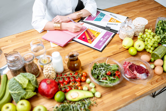 Dietitian writing diet plan, view from above on the table with different healthy products and drawings on the topic of healthy eating