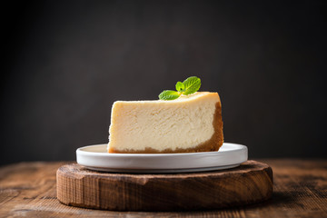 Slice of cheesecake with mint leaf on wooden cake stand over black background. Copy space for text