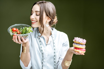 Young woman nutritionist looking on the salad choosing between healthy food and sweet dessert on the green background