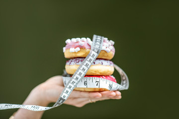 Three sweet donuts covered with measurement tape on the hand on the green background. Unhealthy eating and adiposity concept