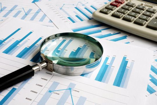 Business papers with financial report and magnifying glass. Audit concept.