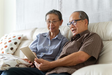Senior couple sitting on sofa in home playing tablet and relaxing together. They are smiling and enjoy to spend their time together with happiness. Happy retirement life concept.