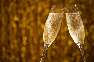 Glasses of champagne on a golden background, party or holiday concept