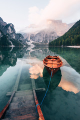 On the pier. Wooden boat on the crystal lake with majestic mountain behind. Reflection in the water