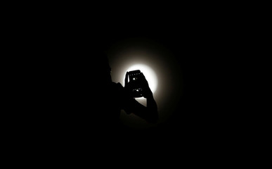 "A resident takes a picture during a total lunar eclipse known as the ""Super Blood Wolf Moon"", in Brasilia"