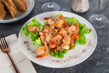 salad with Royal prawns on a white plate on the dark surface of the table with Cutlery.