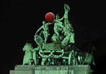 """The moon is seen beside a quadriga on the top of the Cinquantenaire arch during a total lunar eclipse known as the """"Super Blood Wolf Moon"""", in Brussels"""