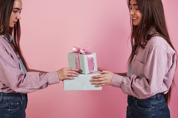 Side view. Close up photo of two girls holding gift boxes at pink background in studio