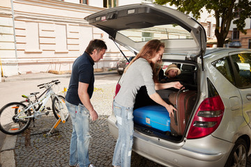 young family is packing the suitcases in the trunk of a ca