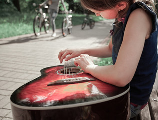 little girl with guitar sitting on a Park bench